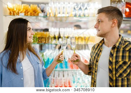 Couple at shelf with wineglasses, houseware store