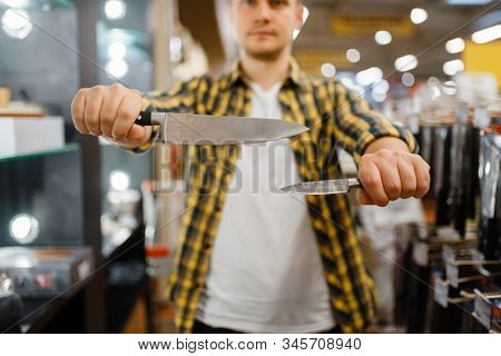 Young man holds kitchen knives in houseware store