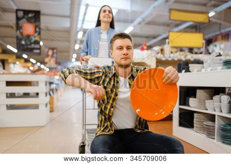 Young couple riding on cart in houseware store