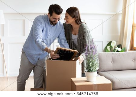 Excited Young Couple Unpack Boxes Settle At New Home