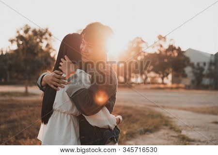 Attractive Young Women Lgbt Lesbian Romantic Couple Hugging In Beautiful Sunset With Lens Flare.