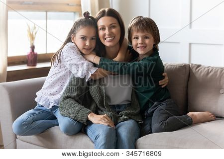 Little Kids Relax On Couch Cuddle With Young Mum
