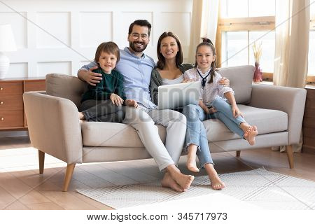 Happy Young Family Sit On Couch Using Modern Laptop