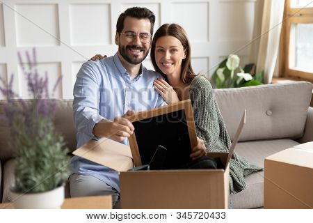 Smiling Couple Unpack Boxes Settling At New Home