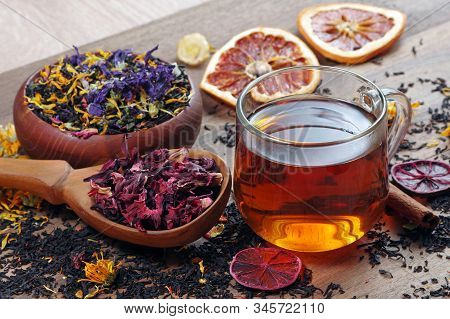 Cup Of Fresh Tea And Different Varieties Of Tea Leaves On A Wooden Table. Blended Tea With Flower Pe