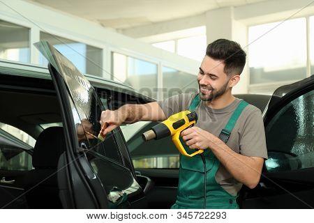 Worker Tinting Car Window With Heat Gun In Workshop