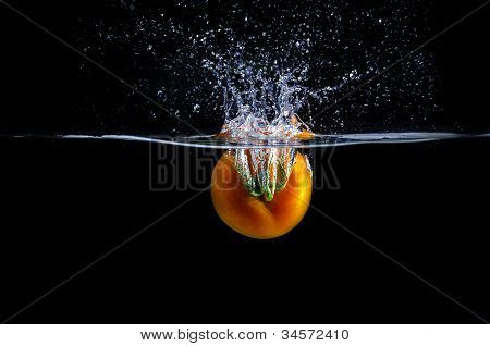 red tomato splashing in water