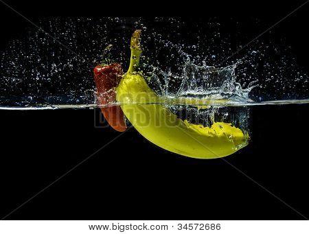 Yellow banana and red fresno pepper, splashing in water