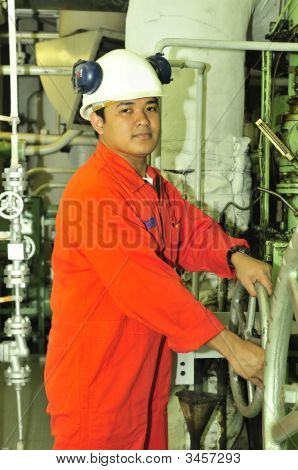 A shipping engineer near a panel of ship's automation poster
