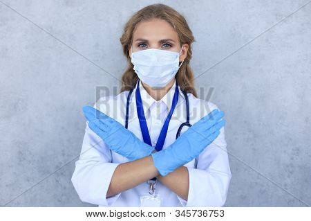 Portrait Of Female Doctor With Stethoscope In Mask Isolated Over Grey Background.