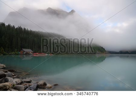 Lake Louise, Canada - August 17, 2019: Panoramic Image Of Quiet Lake Louise Under Morning Fog On Aug