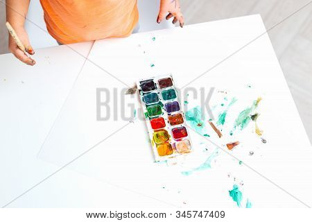 Baby Hands Hold A Brush And Watercolor Paints. Baby Art. Copy Space. Flat Lay