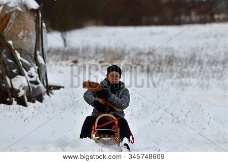 Woman Sledding Downhill On Snow In Winter And Laughing With Domestic Cat In Her Arms