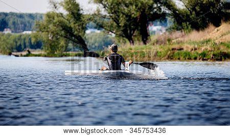 Back Athlete Kayaker Rowing In Lake. Kayak Competition Race