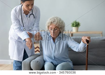 Nurse Helping Older Woman With Walking Cane To Get Up