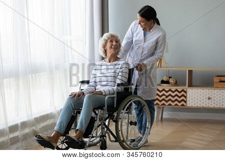 Caregiver Helping Disabled Older Woman In Wheelchair At Home