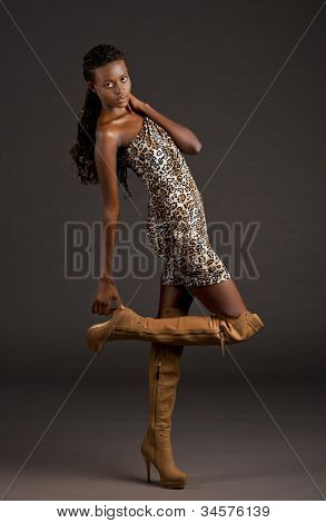 A young Beautiful black woman in a dress and boots