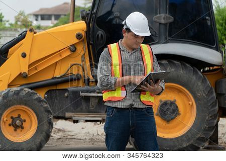 Engineering Wearing A White Safety Helmet Standing In Front Of The Backhoe Looking At Home Construct