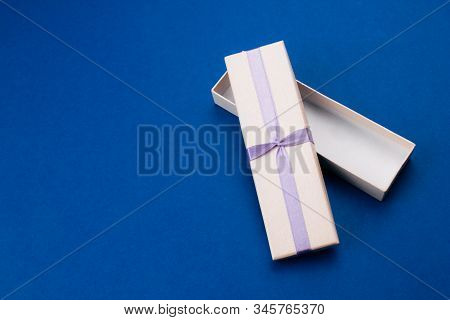 Small Empty Open Gift Box With Purple Ribbon Flat Lay On Trendy Blue Background. Top View Compositio