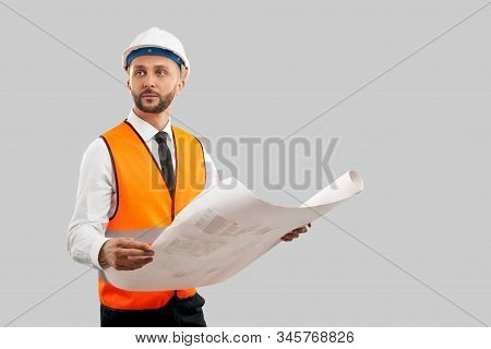 Front View Of Young Bearded Architect In Orange Reflective Vest And Helmet Holding Big Map. Engineer