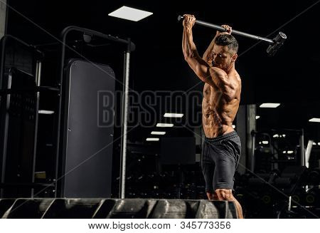 Side View Of Strong Muscular Man Hitting Giant Tire With Big Sledgehammer. Motion Of Shirtless Cauca