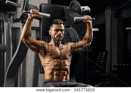 Close Up Of Young Muscular Man On Simulator In Gym. Fit Shirtless Bodybuilder With Perfect Tensed Bo