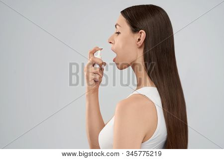Side View Of Young Pretty Brunette Woman With Long Hair Using Spray For Throat. Isolated Crop Of Fem