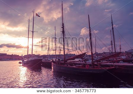 Wooden Sailing Boats At The City Pier Against A Surreal Purple Sky