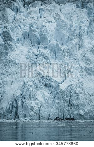 Close Up Shot Of Huge Glacier Wall. Large Chunks Of Ice Breaking Off. Moody And Overcast Weather. Eq