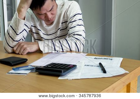Selective Focus Of Adult Asian Man Looking His Invoices And In Trouble From Overdue Credit Card Expe