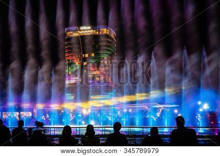 Tashkent, Uzbekistan - 30 October, 2019: People Watch Dancing Fountain Illuminated At Night In New T