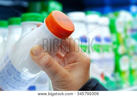 Buyer Checks Expiration Date Of Dairy Product Before Buying It. Womans Hand Holding Milk Bottle In S