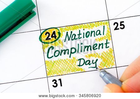 Woman Fingers With Pen Writing Reminder National Compliment Day In Calendar. January 24.