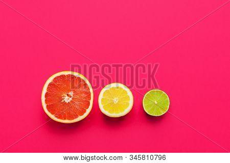 Slices Of Juicy Ripe Citrus Fruits Lemon Lime Grapefruit Arranged As Stoplight On Fuchsia Pink Backg