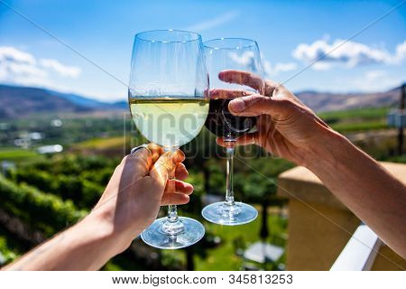 Happy Couple Hands Cheering Red And White Wine Glasses From A Winery Tasting Room Terrace Against Gr