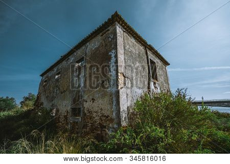 A Wide-angle View Of A Desolate Dilapidated Stone Building In A Small European District Alcochete, P