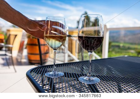 White And Red Wine Glasses On The Table, Hand Choosing And Holding White Glass, Selective Focus And