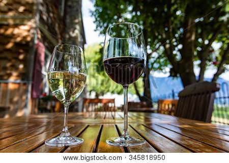 Pair Of Different Glass Sizes And Wines, Red And White Wine Glasses On Wooden Furniture Table Close