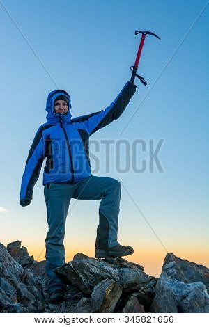 Female Mountaineer Celebrating Successfull Ascend With Ice Axe Raised Into The Sky.