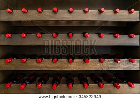 Lines Of Wine Bottles With A Red Seal, Stored On A Wooden Rack, Tasting Room Wines Display, Tasting