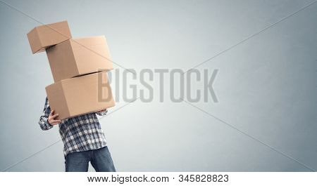 Man holding heavy cardboard boxes relocation, moving house or courier delivery background