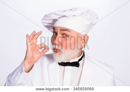 Old Chef Showing Ok Sign. Professional Chef Man In Restaurant Showing Sign Delicious. Male Chef Gest