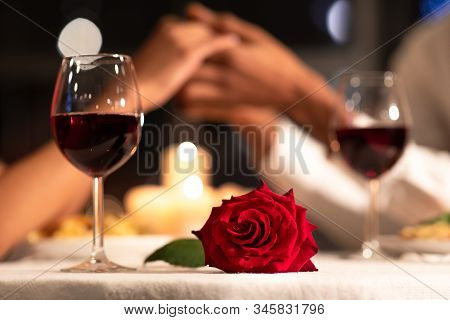 Romantic Date. Red Rose Lying On Table, Loving Afro Couple Holding Hands During Valentines Dinner In