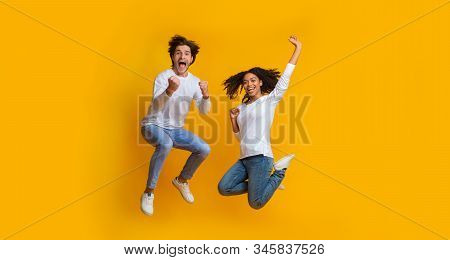 Unbelievable Sales. Overjoyed Multiracial Couple Jumping In The Air And Celebrating Success, Cant Be