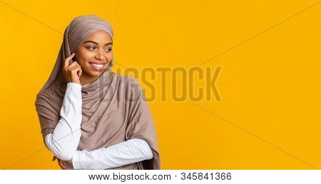 Interested Afro Arabic Girl In Hijab Looking Away At Copy Space On Yellow Background And Touching He