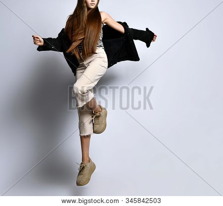 Brunette Adolescent With Long Hair, In Striped T-shirt, Black Denim Jacket, Beige Pants And Sneakers