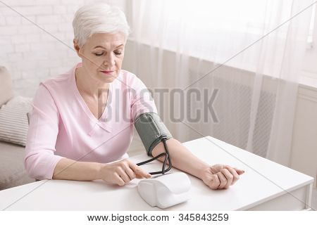 Senior Lady With Hypertension Measuring Blood Pressure Herself, Empty Space
