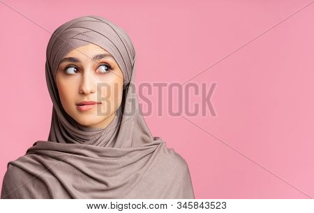 Closeup Portrait Of Uncertain Muslim Girl In Hijab Biting Lip And Looking Away At Copy Space Over Pi