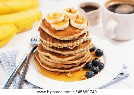 Pancakes With Banana And Golden Maple Syrup On White Plate Closeup View. Sweet Breakfast, Stack Of F