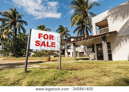 White For Sale Sign With A House In Background. For Sale Inscription On The Plate